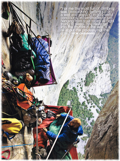 Picture of men who are rock climbing sleeping in sleeping bags while hanging off of a cliff.