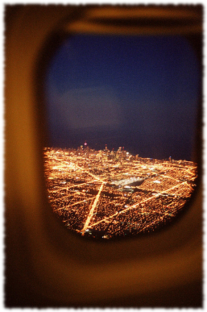 View through a plane window while landing showing a mass of city lights to the travelers.
