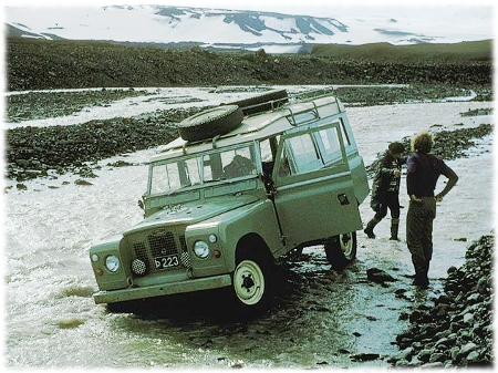 Picture of a jeep stuck in a river in Iceland with two people standing next to it.