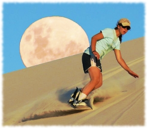 Picture of a woman sandboarding down a sand dune with the moon rising behind the sand.