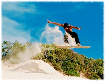 Picture of a man doing a jump and flying through the air while sandboarding.