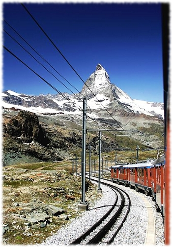 Picture out the window of a train car of the Gornergrat Bahn, a railway in the Alps Mountains.
