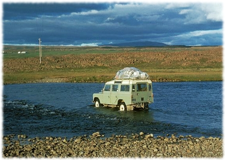 Picture of a jeep traveling through a river in Iceland with travel gear on the roof.
