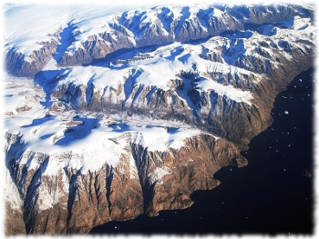 Picture of the icy snow an mountains of Greenland, with a noticeable absence of green.