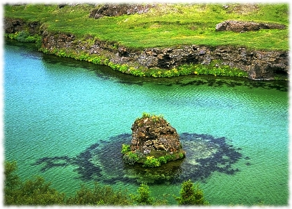 Picture of green grass an clear waters in Iceland.