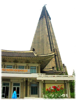 A picture of the Ryugyong hotel in North Korea with a woman exiting from a door in a building in front of it.