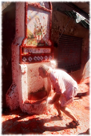Picture of the La Tomatina festival with a man taking cover from the onslaught of tomatoes.