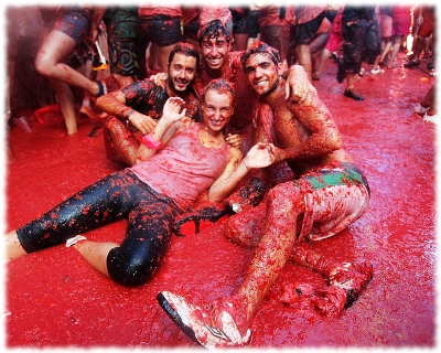 Picture of a group of tourists posing in tomatoes during the La Tomatina festival in Bunol, Spain.