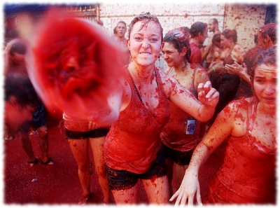 Picture of a woman throwing a tomato at the camera during the La Tomatina festival which is held in Bunol Spain.