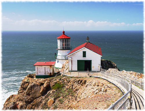 Picture of the Point Reyes lighthouse and the turbulent ocean water behind it.